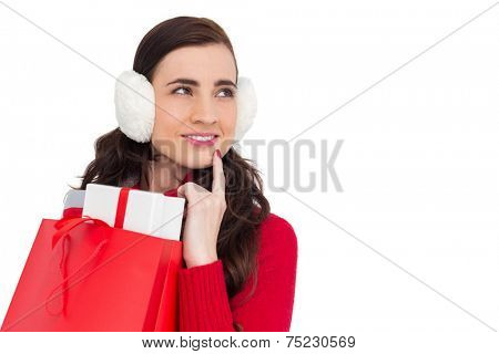 Brunette with ear muffs holding shopping bag full of gifts on white background