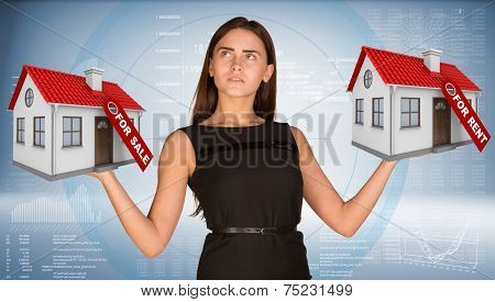Businesswoman holding two house with tags for sale and rent