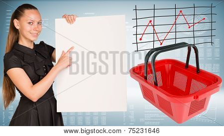 Beautiful businesswoman in dress smiling and holding empty paper sheet. Red shopping basket are loca