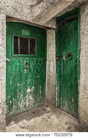 Two old green timber doors in the scuffed wall