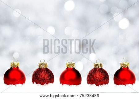 Red Christmas baubles in snow with silver background