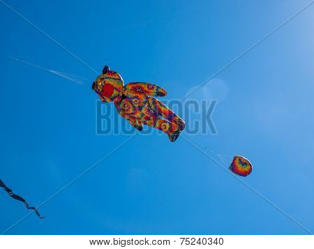 Colorful Tie Dye Bear Kite Flying In Cloudless Blue Sky