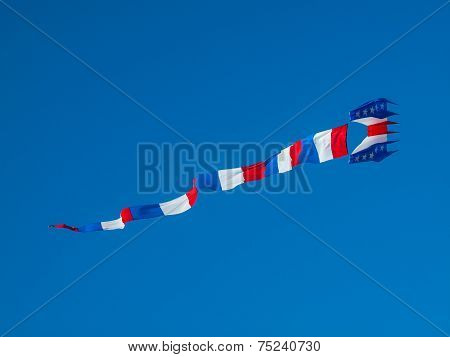 Red, White, And Blue Kite Flying In Cloudless Blue Sky