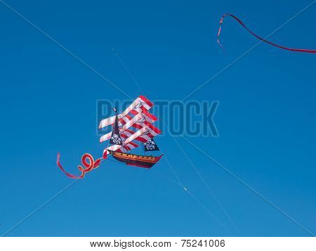 Colorful Pirate Ship Kite Flying In Cloudless Blue Sky