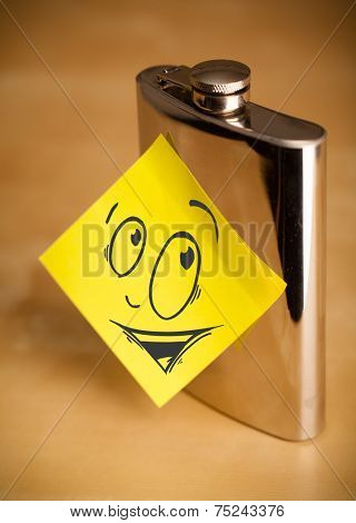 Drawn smiley face on a post-it note sticked on a hip flask