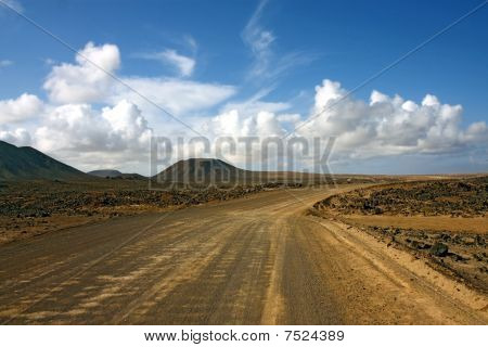 dasty road in desert under cloudy sky