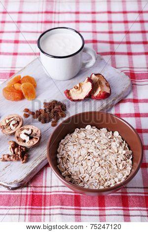 Bowl of oatmeal, mug of yogurt, marmalade, chocolate, raisins, dried apricots and walnuts on wooden cutting board on checkered fabric background