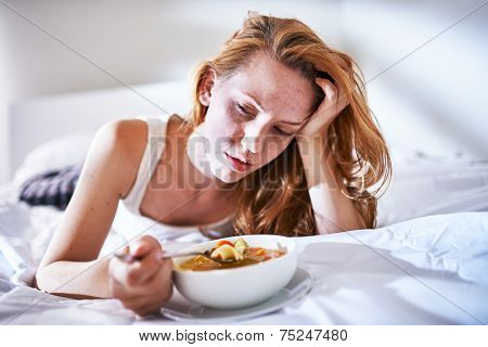 eating chicken noodle soup in bed while sick