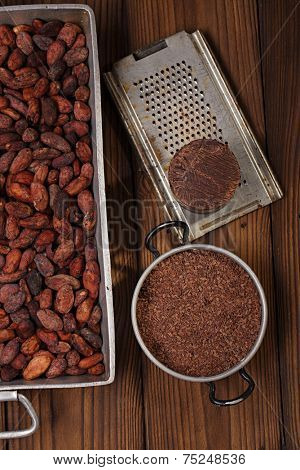 grated dark chocolate in tin with cocoa beans and solid piece in old texured wood