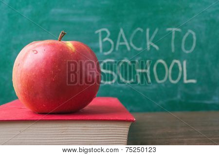 Apple on the book and Back to School handwritten on the chalkboard in the background