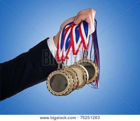 Businessman's Hand Holding Medals Over Blue Background