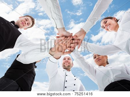 Waiters And Waitresses Stacking Hands