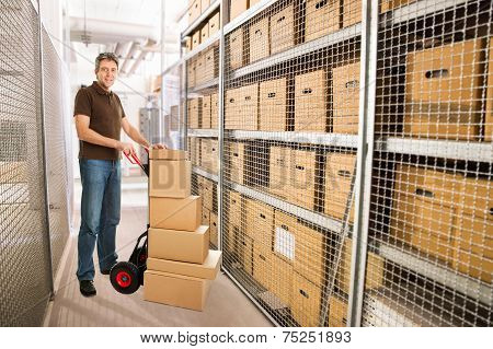 Delivery Man With Hand Truck And Stack Of Boxes