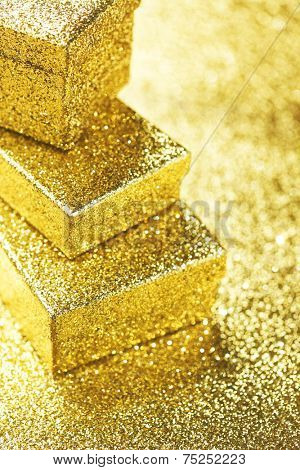 Stack of Gold decorative boxes with holiday gifts on abstract gold background
