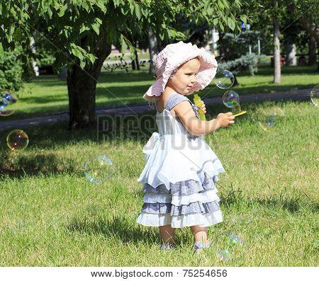 Little girl blowing soap bubbles in city park.