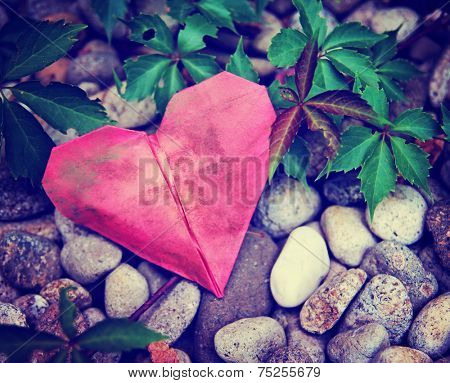 a discarded paper heart on a rock and ivy vine background toned with a retro vintage instagram filter effect