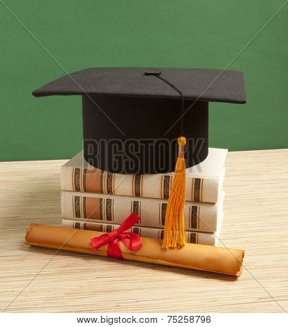Gortarboard and graduation scroll, on a stack of old battered book