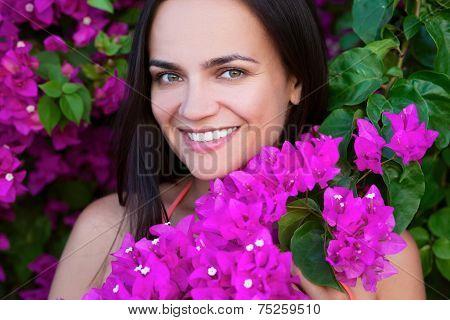 Portrait Of Young Beautiful Woman Girl On Background Of Bougainvillaea Purple Violet Flowers In Blos
