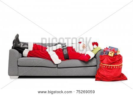 Santa sleeping on sofa with a bag of presents beside him isolated on white background