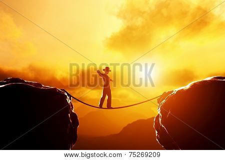 Man in hat walking and balancing on rope over precipice in mountains at sunset. Concept of business, risk taking, challenge, concentration.