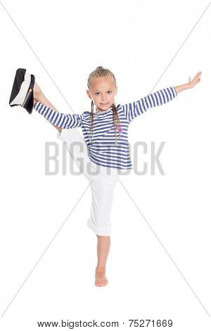 Little girl dressed as a sailor boy performs gymnastic exercise. Girl is six years old.
