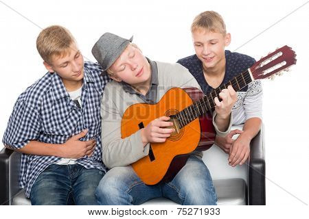 Three friends spend leisure playing guitar. Two of the boys twin brothers.