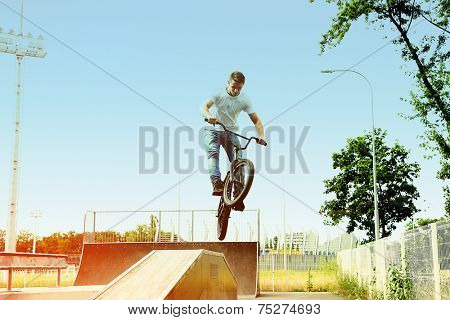 Young boy jumping with his BMX Bike at skate park