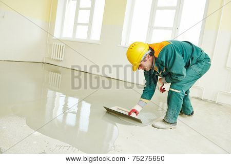 plasterer during floor covering works with self-levelling cement mortar