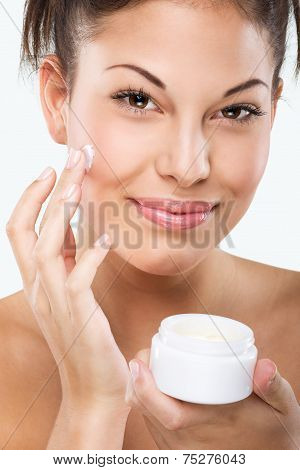 Flawless skinned woman with moisturizing face cream
