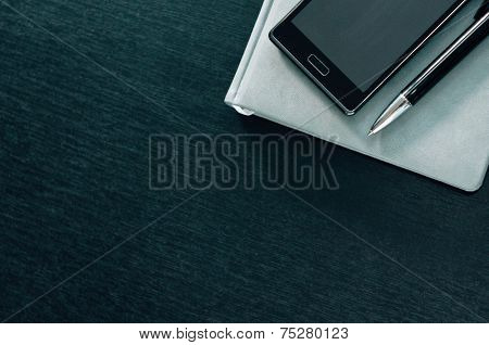 Planner With Phone On A Black Background