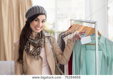 Smiling brunette holding price tag on shirt at clothes store