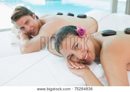 Side view portrait of a young couple enjoying stone massage at health farm