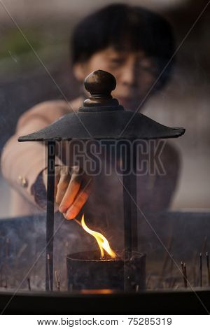 NARA,JAPAN, NOVEMBER 18, 2011 : A Japanese woman is igniting an incense stick before praying at the Todai-ji temple in Nara near Kyoto.