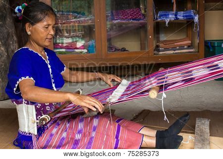 MAE KLANG LUANG, THAILAND, JULY 17, 2013: A women from a minority Karen tribe is weaving cotton with a traditional tool in the village of Mae Klang Luang, Thailand