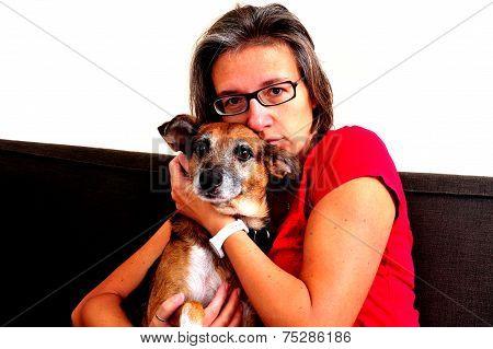 Woman Cuddling With Dog On A Grey Sofa