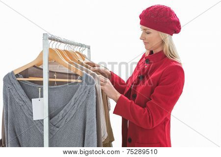 Pretty blonde looking at clothes on rail on white background