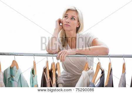 Pretty blonde looking through clothes rail on white background