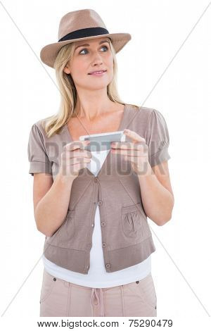 Happy blonde in trilby holding phone on white background