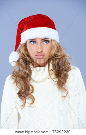 Charismatic attractive young blond woman wearing a red Santa hat pulling a whimsical face as she looks to the side  over blue with blue eyes