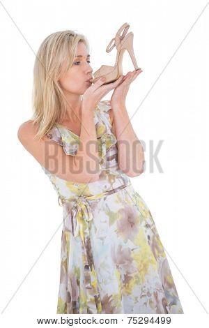 Elegant blonde admiring a shoe on white background