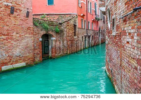 Narrow canal among old brick houses in Venice, Italy.