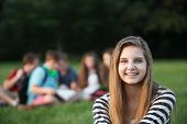 stock photo of braces  - Cute smiling teenage girl with braces sitting outdoors - JPG