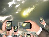 foto of comet  - Hands holding smart phones and shoot video as falling meteorite or comet - JPG