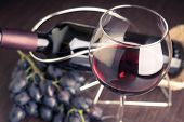 stock photo of merlot  - Glass of red wine with bottle and grapes. Winery background toned image