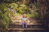 pic of laugh out loud  - Cute baby girl sitting on the stone stairs in the park and holding bottle with drink  - JPG