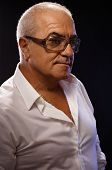 stock photo of 55-60 years old  - Portrait of casual old man in white shirt and glasses over black background - JPG