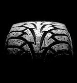 foto of asymmetric  - winter car tyre on a black background - JPG