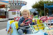 foto of funfair  - a little blond boy playing in a funfair carousel - JPG