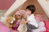 foto of teepee tent  - Toddler child kid engaged in pretend play with stuffed toys and teepee tent - JPG