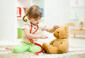 picture of girl toy  - child girl playing doctor and curing plush toy indoors - JPG
